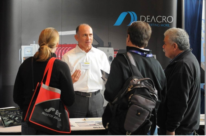 A Deacro employee talking with potential customers at a trade show.